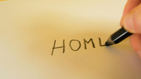 A man's hand writes the words Home with a black pencil on a white background Footage