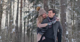 A young man and a woman in a coat are having fun and playing with snow in a Footage