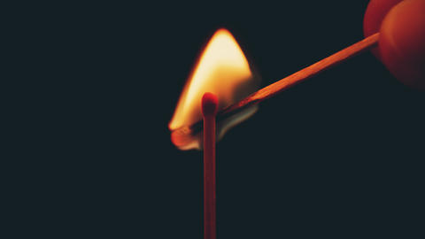Lighting a match with another match in the dark, close-up shot Live Action