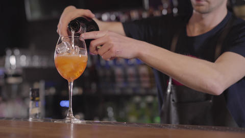Young bartender pouring a refreshing whiskey or alcohol cocktail into a glass Live Action