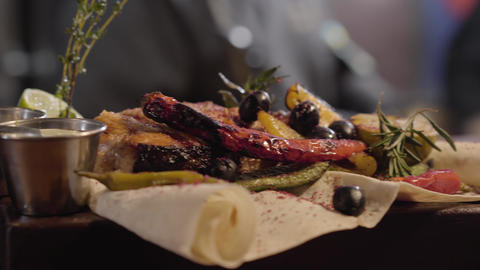 Close up grilled salmon fish served with sauces, herbs, olives, chili pepper Live Action