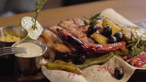 Grilled salmon fish served with sauces, herbs, olives, chili pepper, lime and Live Action
