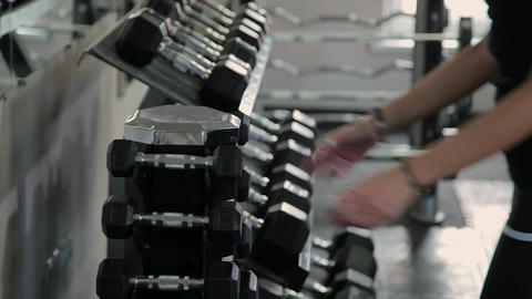 Gym woman strength training lifting dumbbell weights getting ready for exercise Live Action