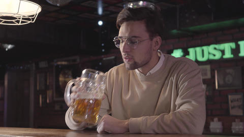Bar visitor sitting behind the bar, drinking beer and… Stock Video Footage