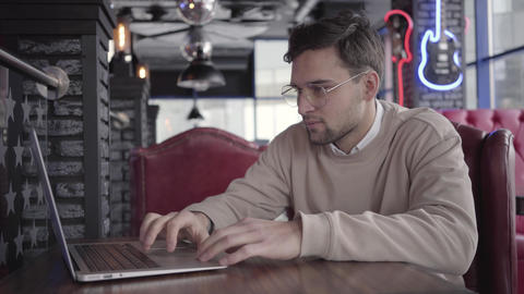 Handsome man working with laptop in modern cafe close up. Stylish confident Footage