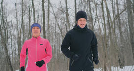 A man and a woman in a pink jacket in the winter running through the Park in Footage