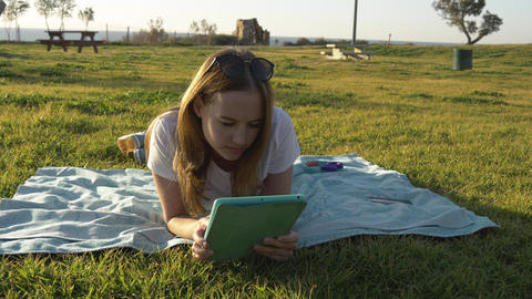 Female using tablet in the park with sea at horizon Footage
