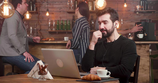 Young man cheer over an achievement while freelancing in a coffee shop Footage