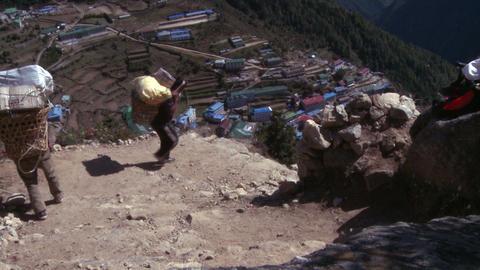 Sherpa porters walking to Namche Bazaar, Nepal carrying baskets Footage