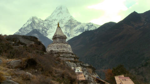 People carrying boxes past a mountainside shrine in the Himalayas of Nepal Footage