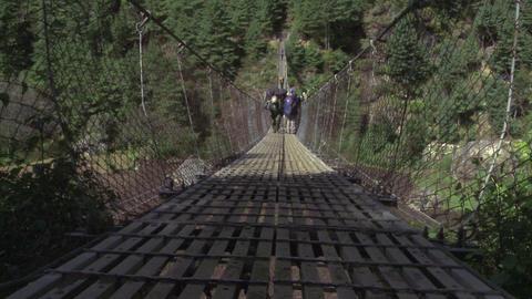 People carrying packs crossing a bridge in Nepal Footage