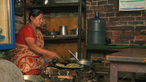 Nepali woman cooking food over a fire Footage