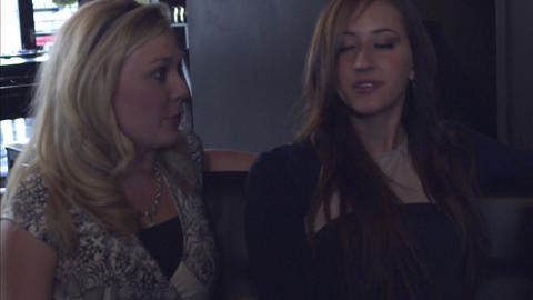 Slow motion handheld shot of two women talking and smiling while sitting on a co Footage