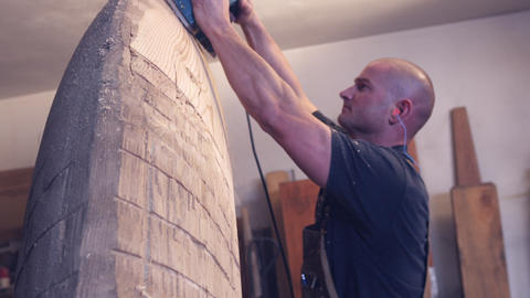 Handheld shot of a woodworker smoothing a wooden sculpture with an electric plan Live Action