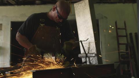 Handheld shot of carpenter grinding metal in his workshop Live Action