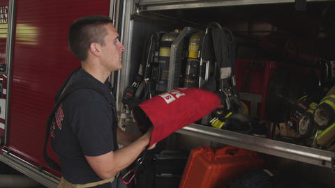 Slow motion handheld shot of fireman doing routine maintenance check on protecti Footage