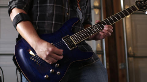 Handheld shot of a man singing and playing an electric guitar Live Action