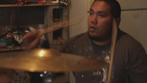Handheld A Latino musician plays his drum set Live Action
