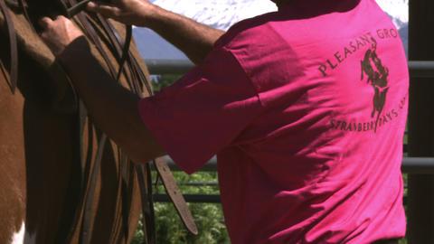 Tilting shot of a cowboy saddling a horse Footage