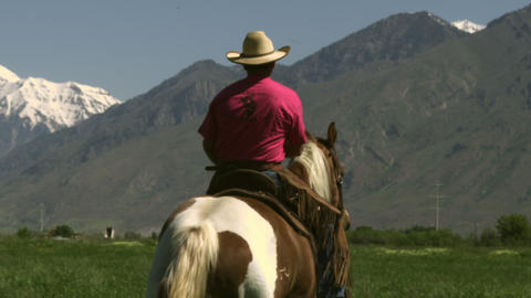 Slow handheld shot of a cowboy riding his horse Footage