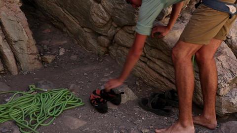 Tilt shot of a rock-climber arraigning his gear Live Action
