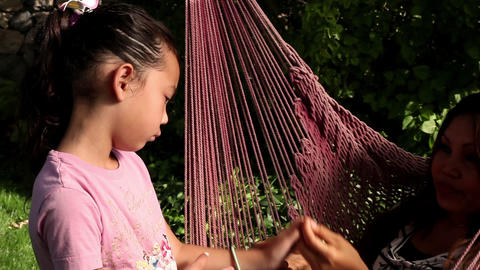Tracking shot of an Asian woman playing with a little girl Footage