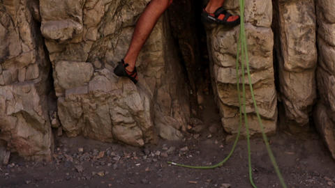 Tilt shot of of a male rock-climber starting his climb Footage