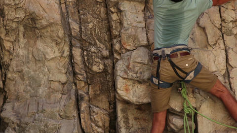 Tilt shot of a man starting his rock climb Footage
