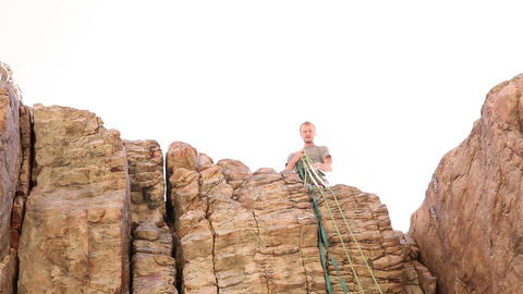 Tilt shot of a rock-climber pulling a rope up a cliff face Live Action