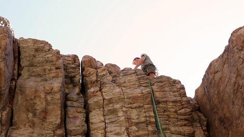 Tilt shot of a rock-climber arranging a rope atop a cliff face Live Action