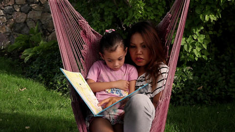 Static shot of a woman and child reading a book while in a pink hammock Footage