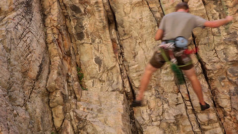 Tilt shot of a rock-climber descending from the top of a cliff Live Action