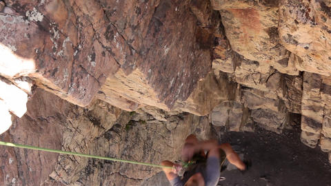 Handheld tilt of a rock-climber struggling up a cliff Live Action