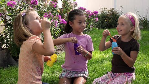 Tracking shot of little girls blowing bubbles in a garden Footage