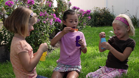 Tracking shot of little girls blowing bubbles in a flowery garden Footage