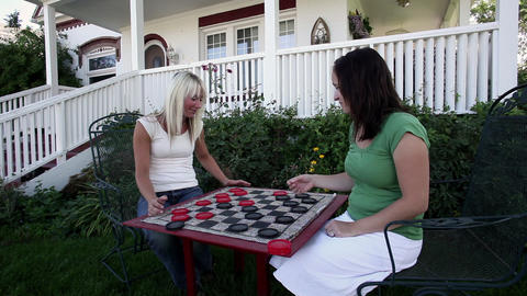 Static shot of two women playing checkers Footage
