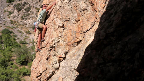 Handheld tracking shot of a rock-climber struggling his way up a cliff Live Action