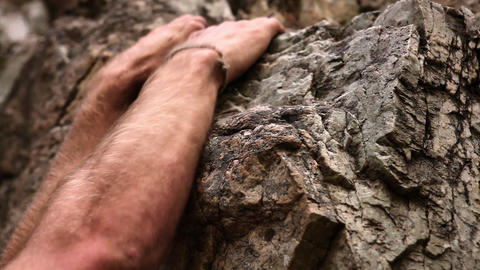 Closeup shot of a man's muscular forearms and his hands on rock Live Action