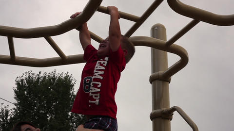 Tracking shot of a small boy hanging from monkey bars with help from his mother Footage