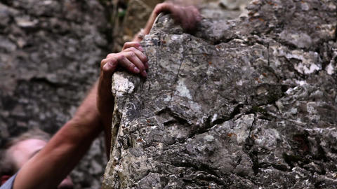 Closeup tracking shot of a man's hands trying to find a solid grip while rock-cl Live Action
