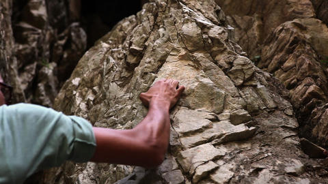 Static shot of a rock-climber's hand grasping craggy rocks Live Action