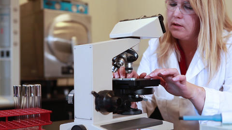 Tracking shot of a lab technician with a microscope Footage