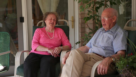 Shot of a happy elderly couple sitting on their porch talking with each other Footage