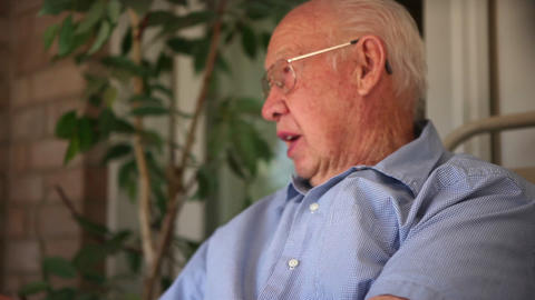 A close up shot at an angle of an elderly man speaking Footage