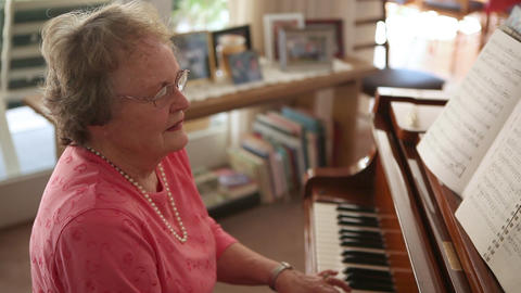 A handheld shot of an senior woman playing the piano Footage