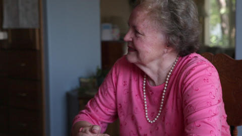 A shot of an elderly couple talking with each other at table in a room with blue Footage