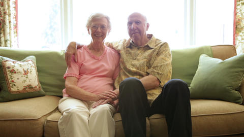 A static shot of an elderly man with his arm around an elderly woman Live Action