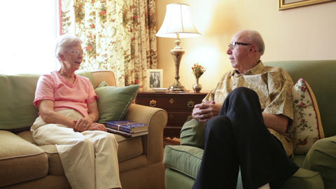 A tracking shot of an elderly couple sitting in a room with yellow walls togethe Footage