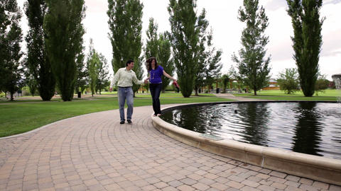 A static shot of a young couple walking around a water fountain together Footage