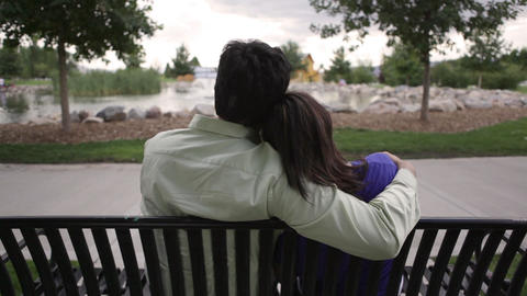 A shot of a young couple sitting on a bench in front of a beautiful pond Footage